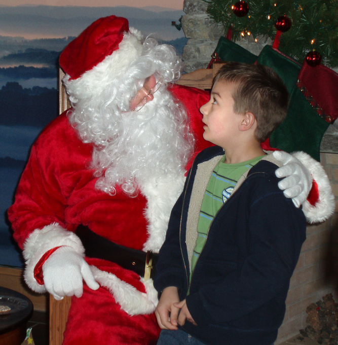 A young boy casts a mesmerized look, amazed he is talking to Santa Claus!